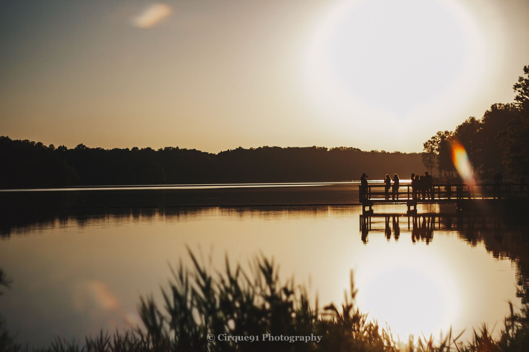 a group of people standing on the dock in reidsville lake during golden hour