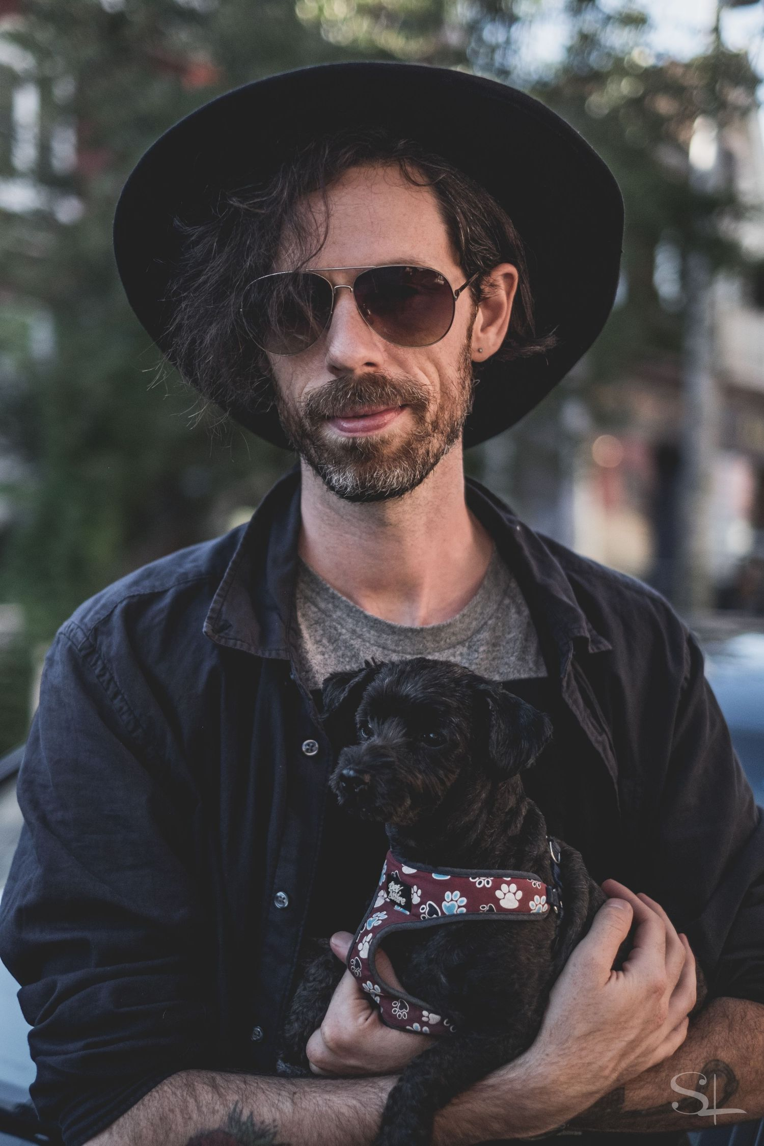 a man with a wide brim hat, dark hair and sunglasses holding a black puppy