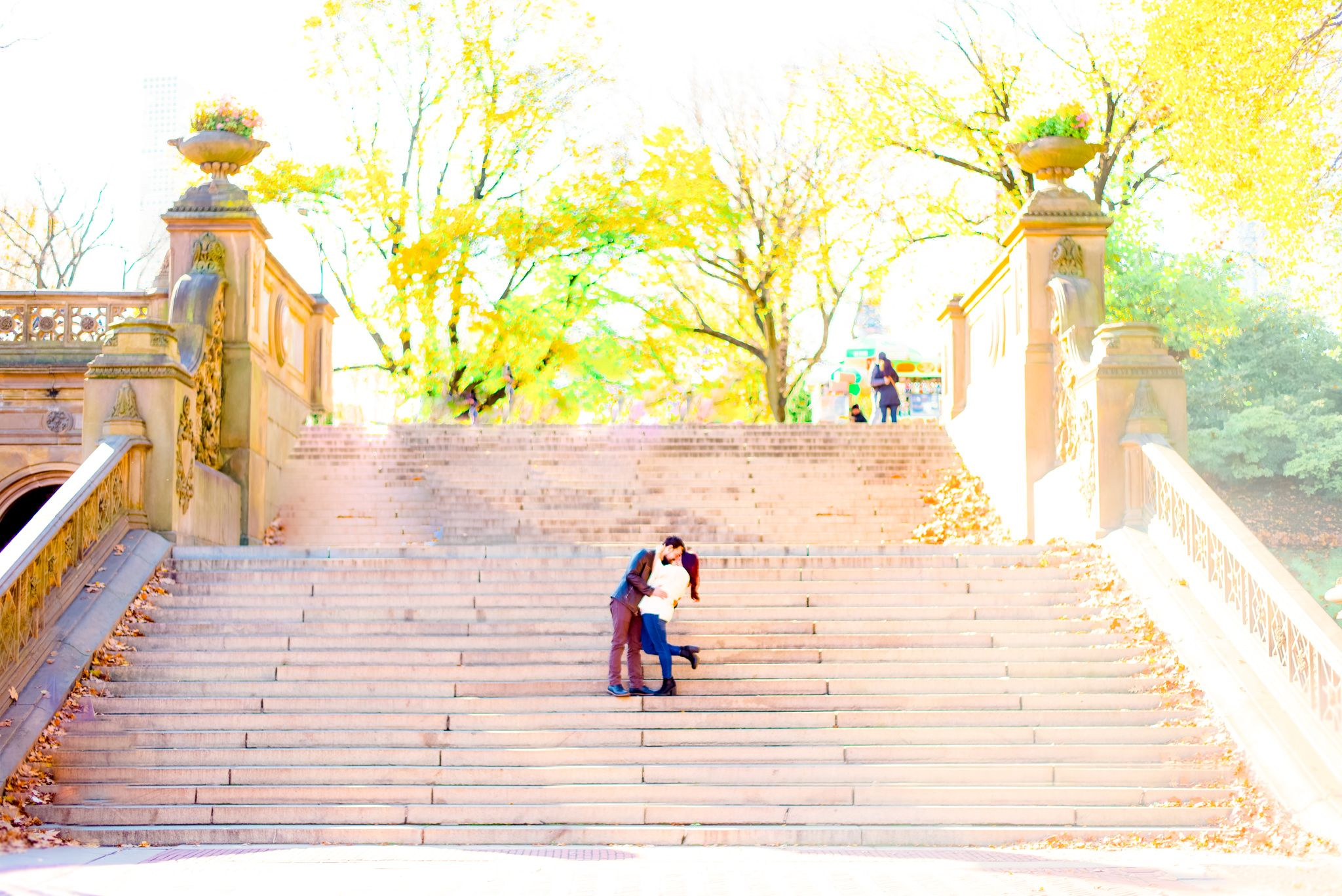 man and woman hugging and dipping in the middle of stairs at Bethesda Terrace in Central Park for sunrise engagement