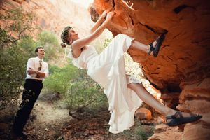 Bride rock climbing and bouldering in southern Utah in her wedding dress.