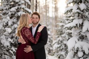 Engagement photos in the snow.  Couple in a snowy pine forest, Big Cottonwood Canyon, Wasatch mountains, Utah.