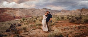 Engagement photo on a canyon ledge with mountains and sand dunes in the background.