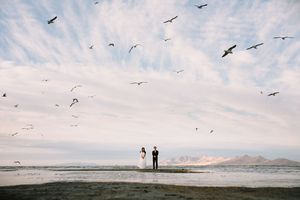 Couple on island in the Great Salt Lake surrounded by seagulls.