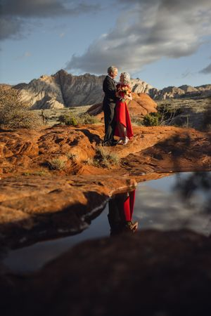 Adventure vow renewal at Snow Canyon State park after a rain storm.  Couple on red rocks in front of white mountains.