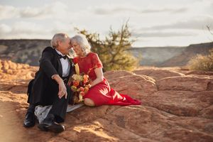 Older couple in the desert.  Woman in a red dress.  Man in Tux.