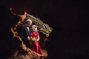 Older couple renewing vows by a red rock arch window.