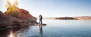 Couple kissing on a red rock ledge in a lake.