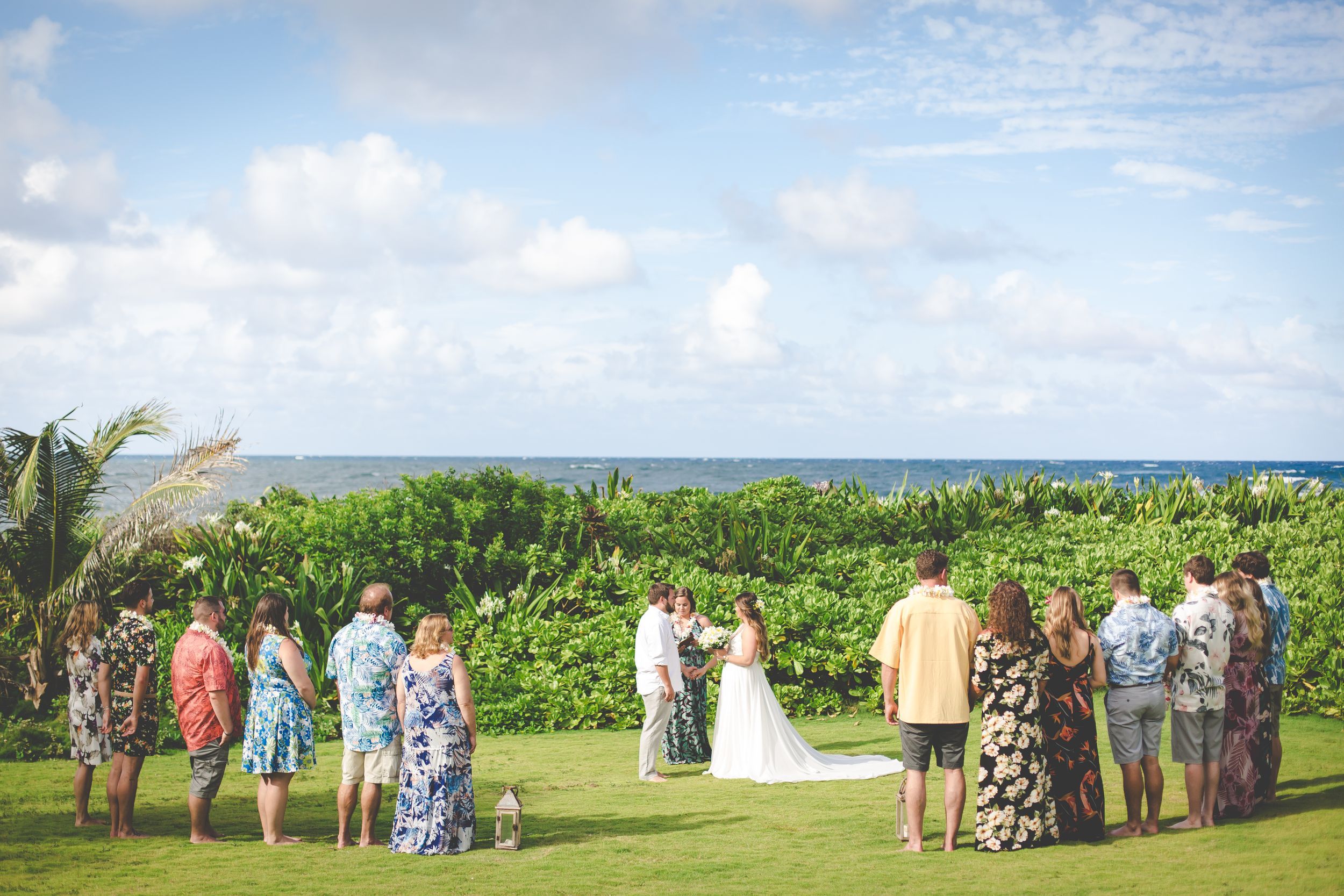 Wide photo of bride and groom holding hands during wedding ceremony. Green grass and plants around them, ocean behind.