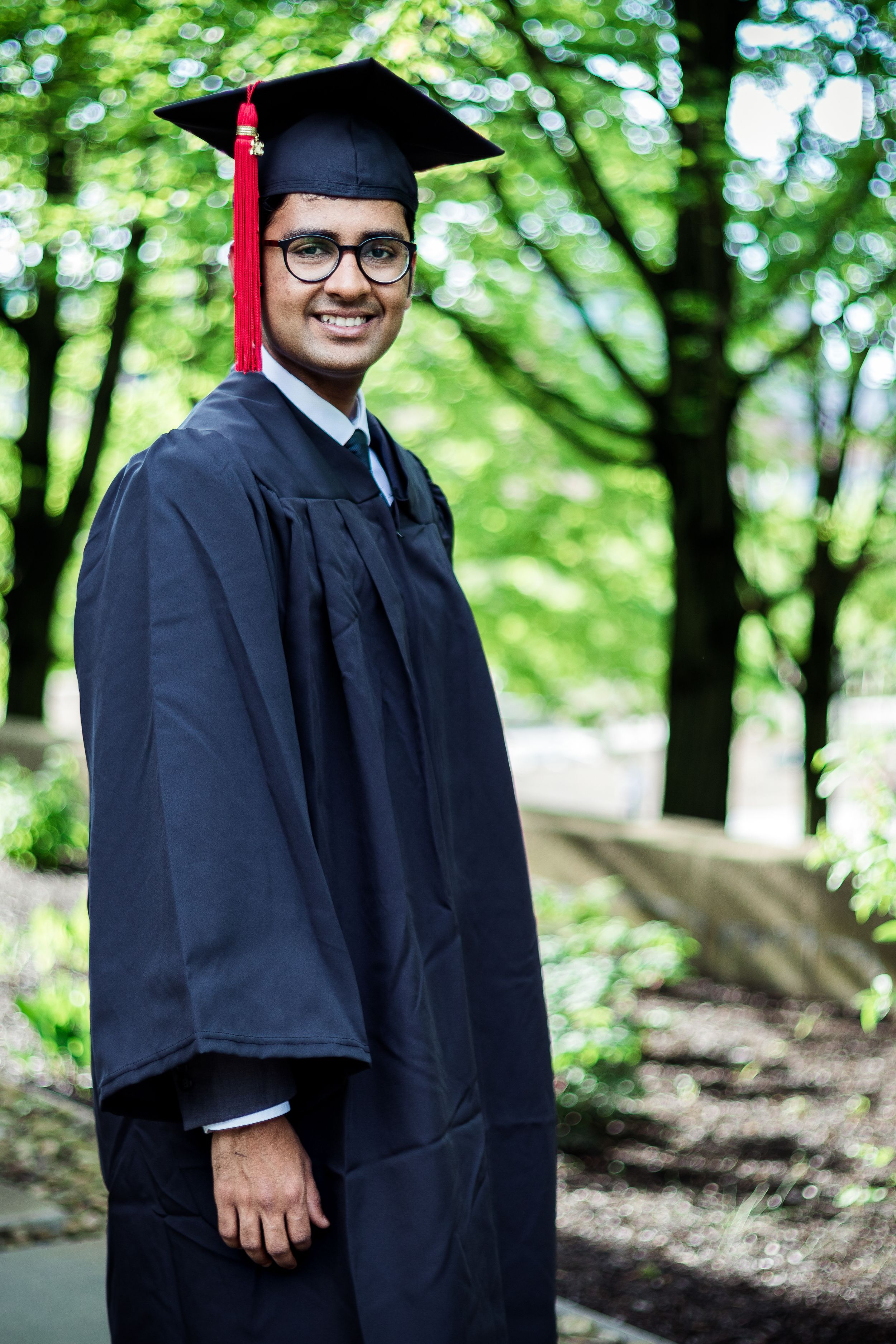 A graduate senior of carnegie mellon university in Pittsburgh PA poses on campus in a graduation cap and graduation gown