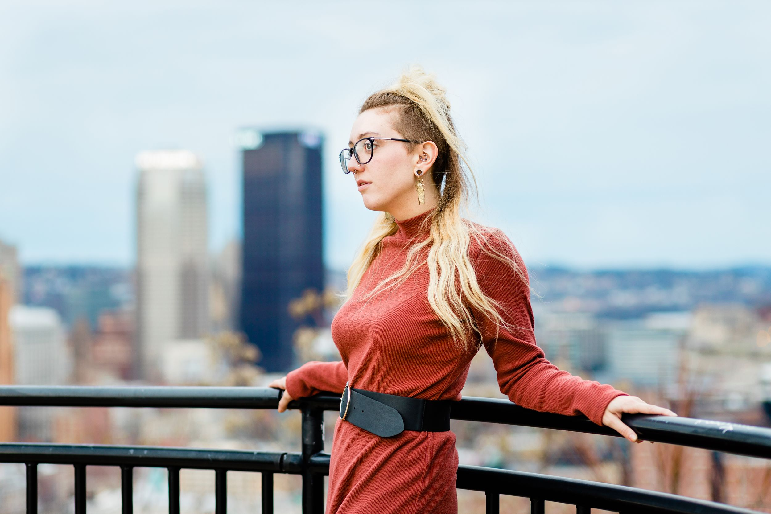 Girl in fashionable orange sweaterdress and beetle earrings poses on a railing in front of the Pittsburgh Skyline