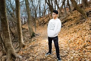 A fashionable asian boy poses in the woods at Emerald View Park in Pittsburgh PA with a strobe light behind him