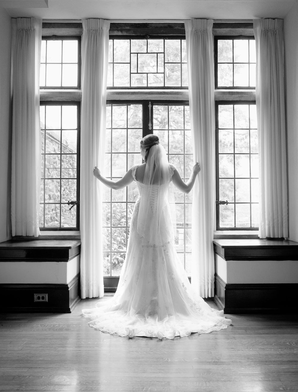wedding photo of bride posing by large window with natural light at Parque Ridley Creek Hunting Hill Mansion