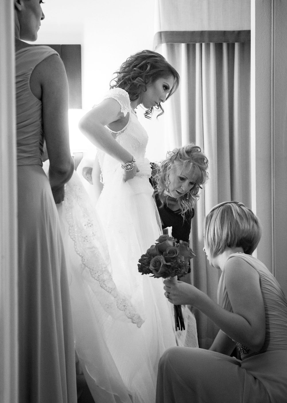 wedding photo of bride getting help with shoes