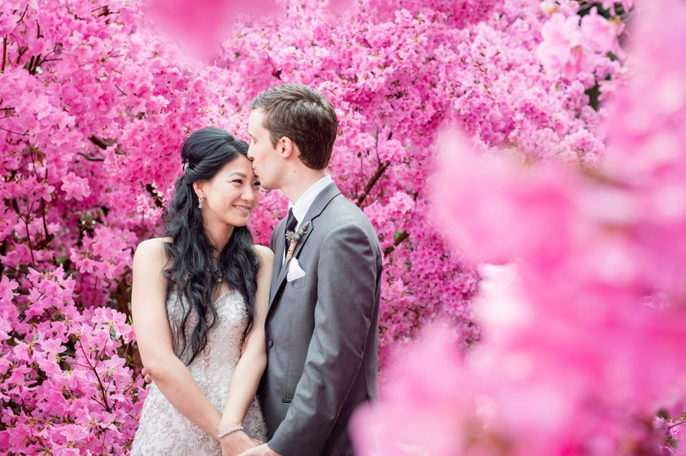wedding photo of bride and groom among colorful blooms at Winterthur Museum in Delaware wedding venue