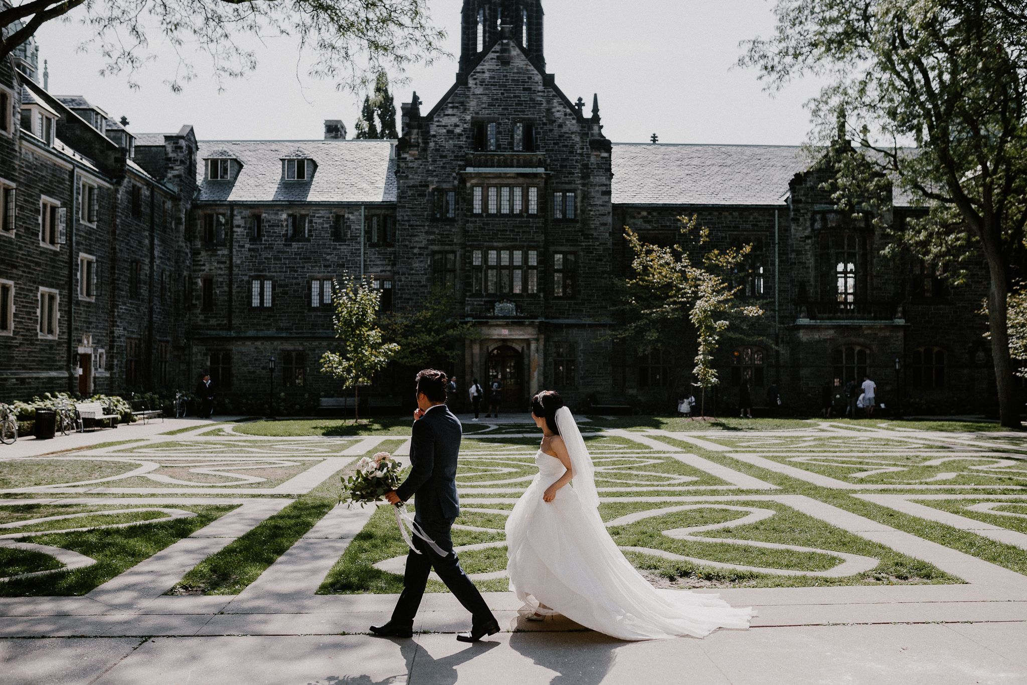 Toronto Asian bride and groom walking in Trinity College garden and groom holding bouquet. Bride wearing Vera Wang dress