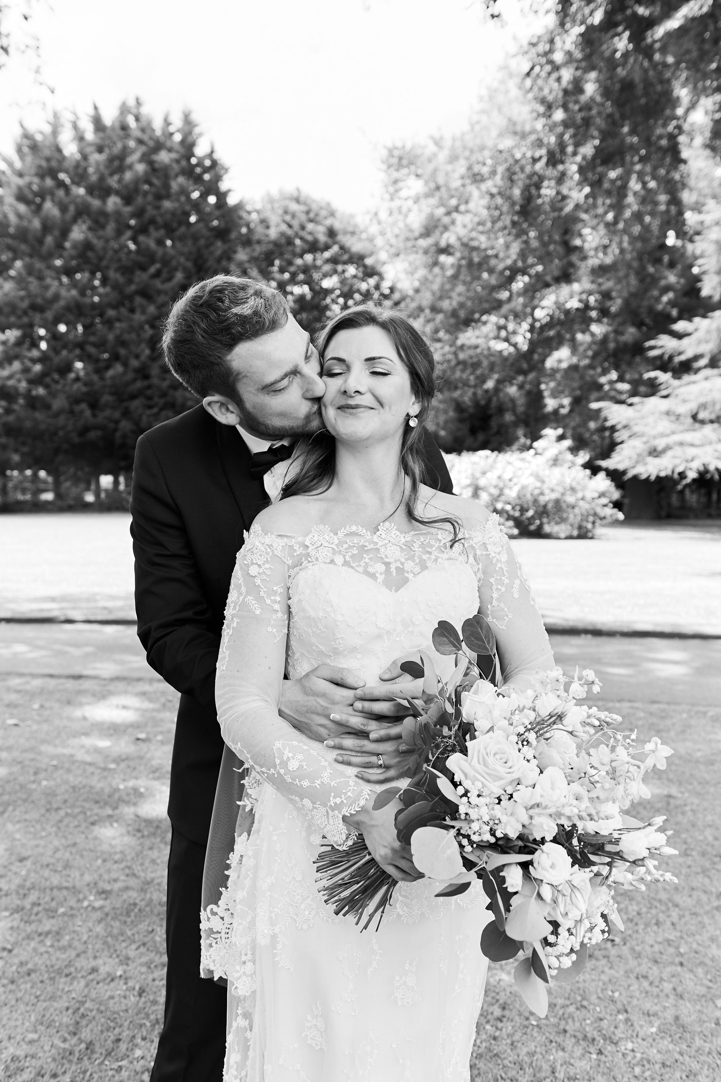 groom kisses bride on cheek as they pose for portraits at Orsett hall, Essex by Norfolk Wedding Photographer Faye Amare