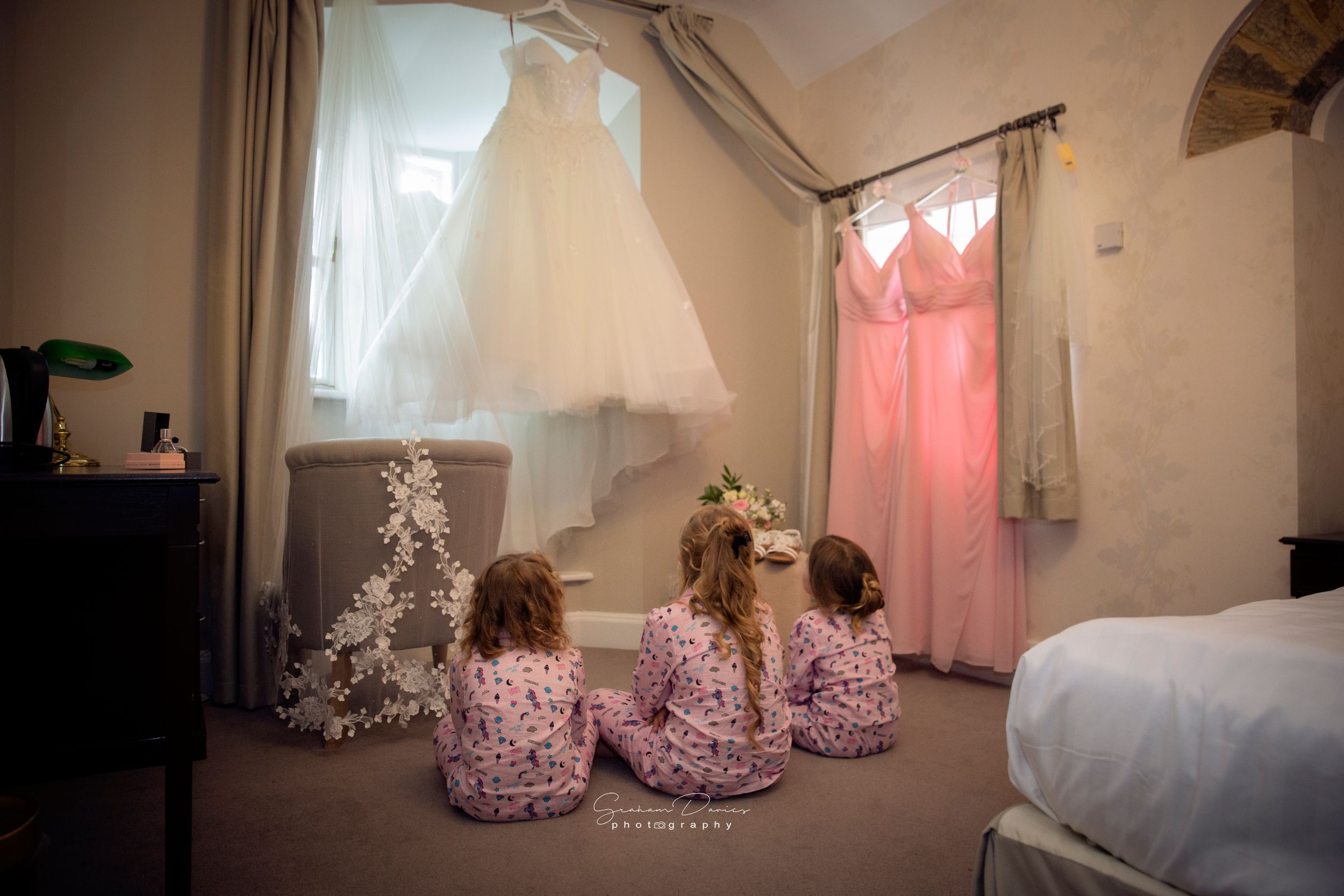 little bridesmaids gathered around the wedding dress at Bryngarw House wedding