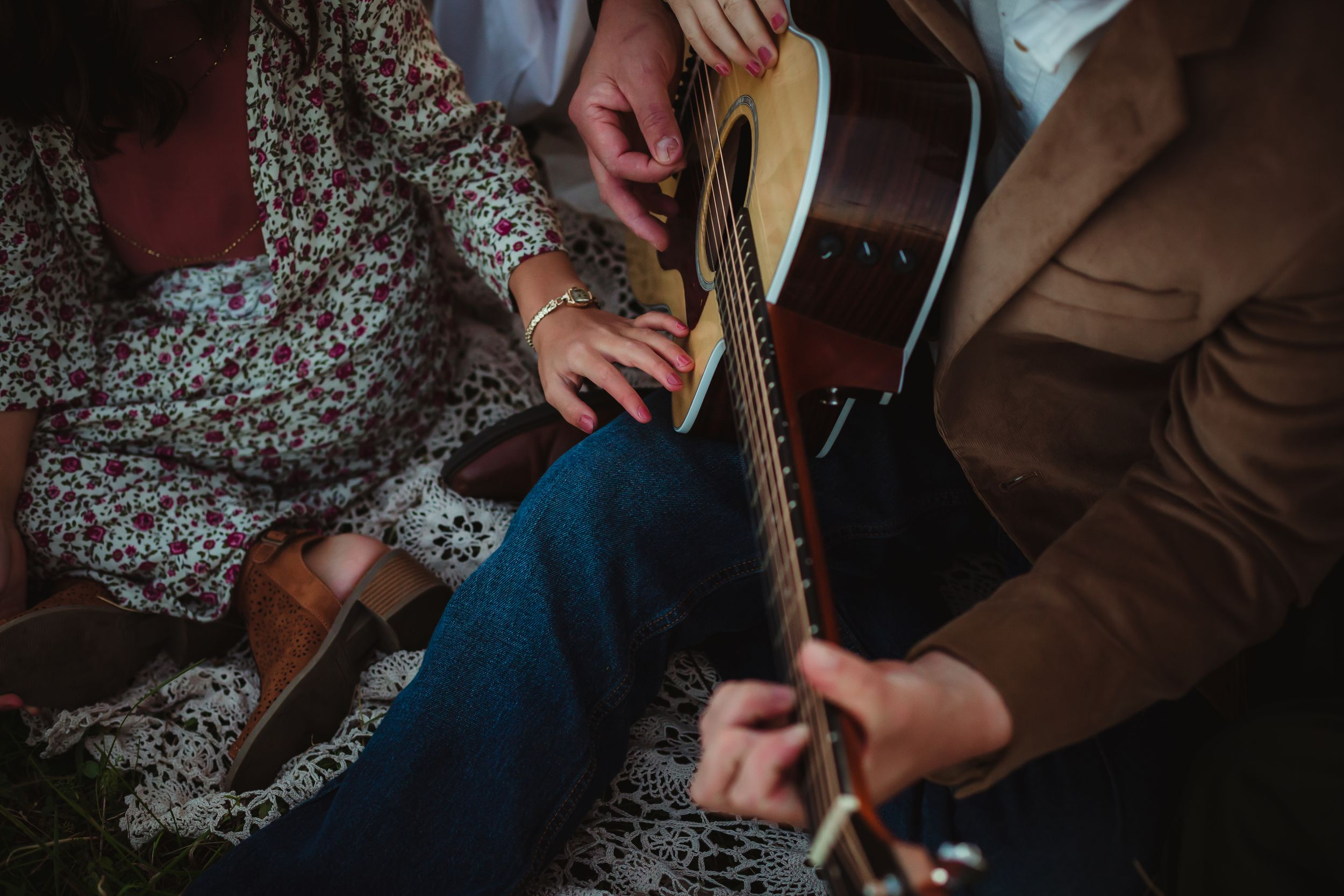 Close up of father and daughter's hands on a guitar.
