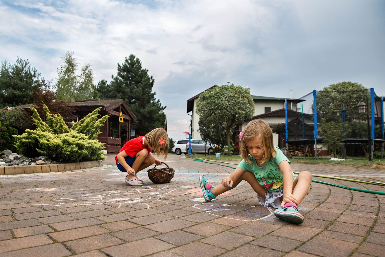 two girls sitting on ground colouring with chalk