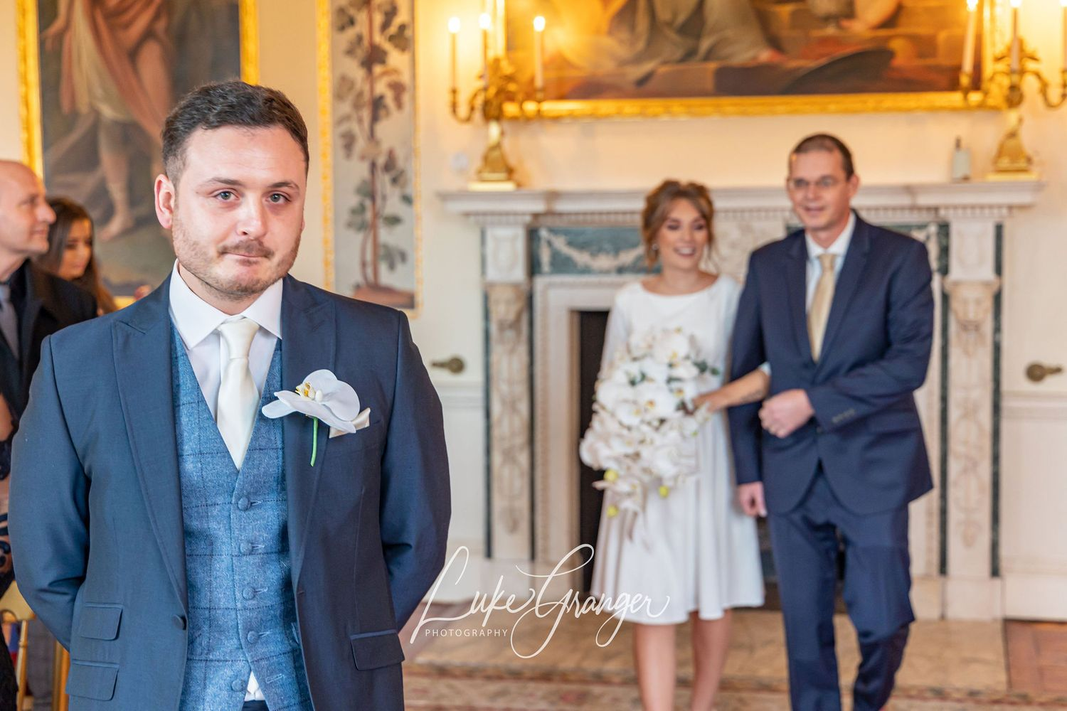 groom looking nervous as bride and her dad walk up the isle