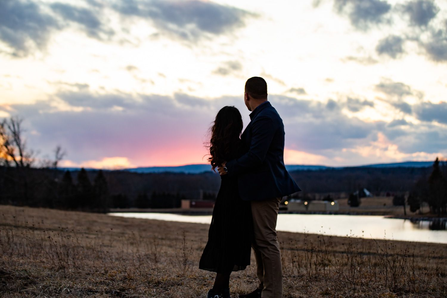 Engaged couple watch the sunset over Watchtower Farms in Wallkill, New York