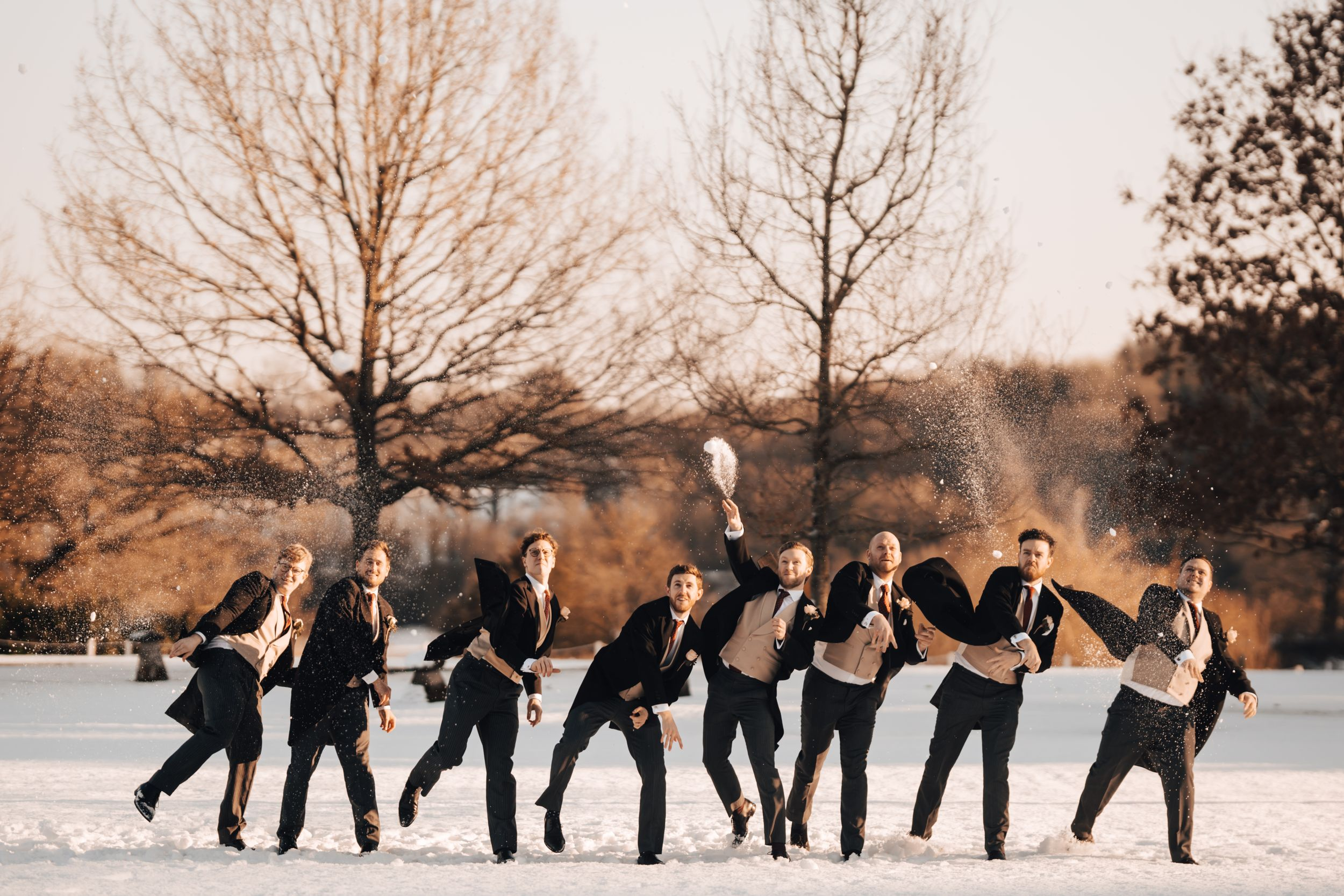 Groomsman snow fight taken at Northbrook Park Wedding Venue in Surrey