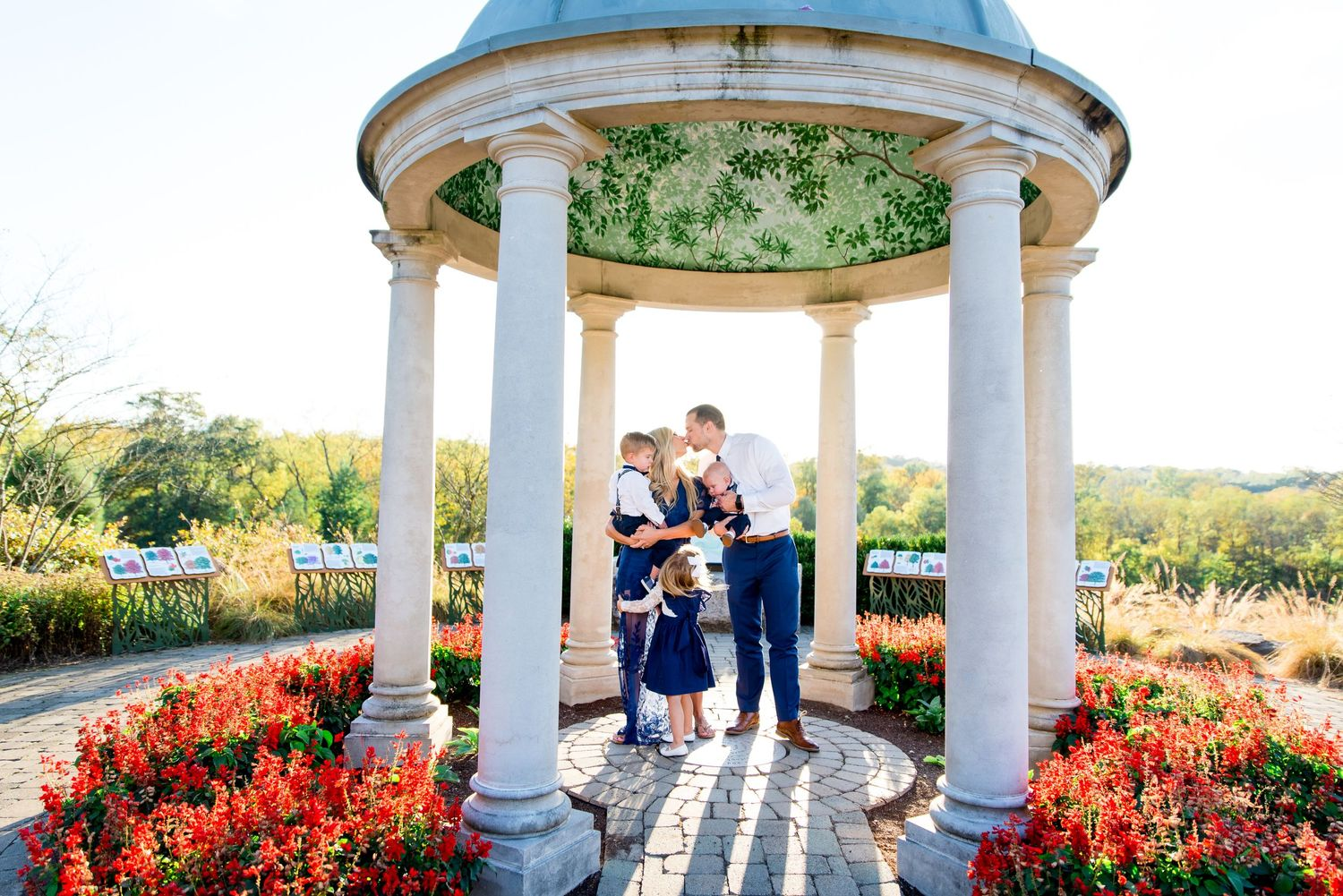 mother and father kissing and holding their three kids under a gazebo at sunset