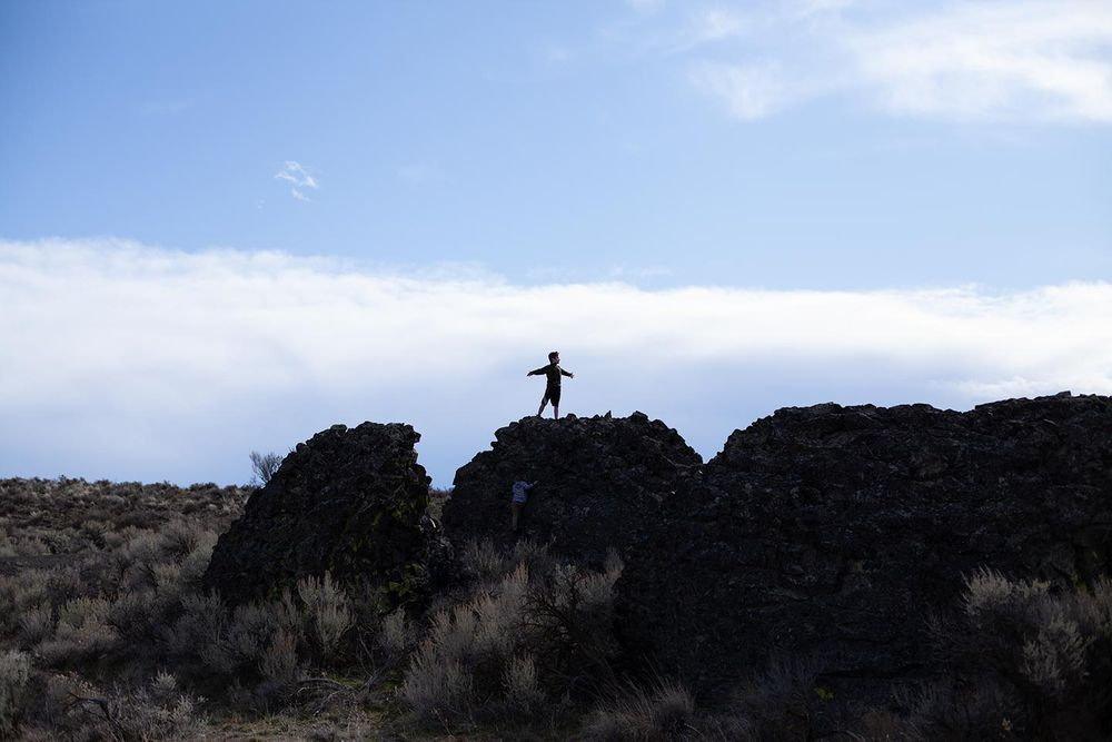 before image of boy standing on rock with outstretched arms