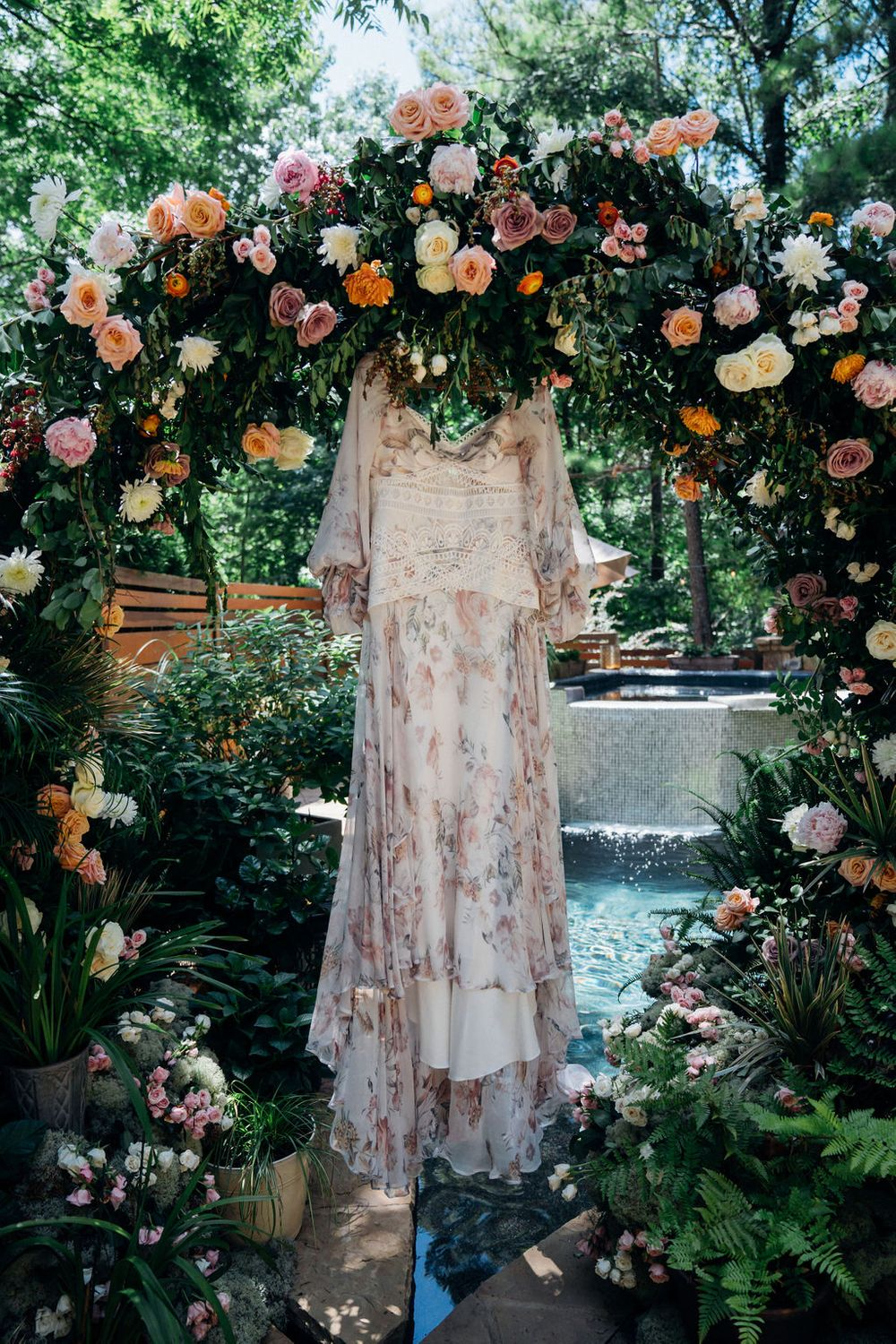 dress hanging in floral arch