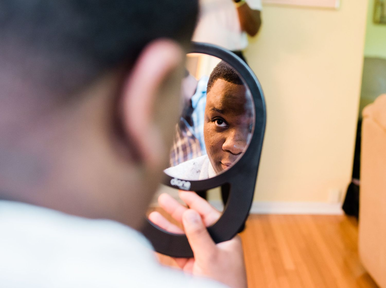 groom looking at himself in mirror