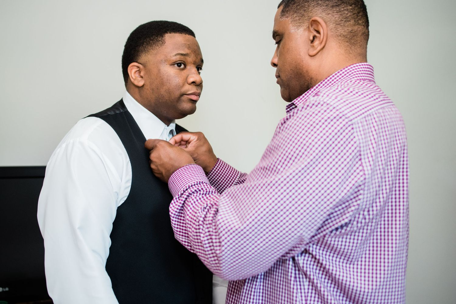father of the groom helping groom with bowtie