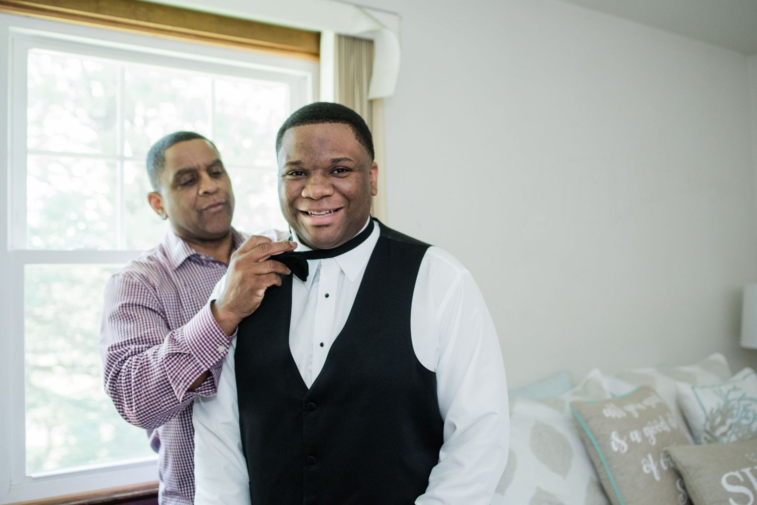 father of the groom helping groom with bow tie