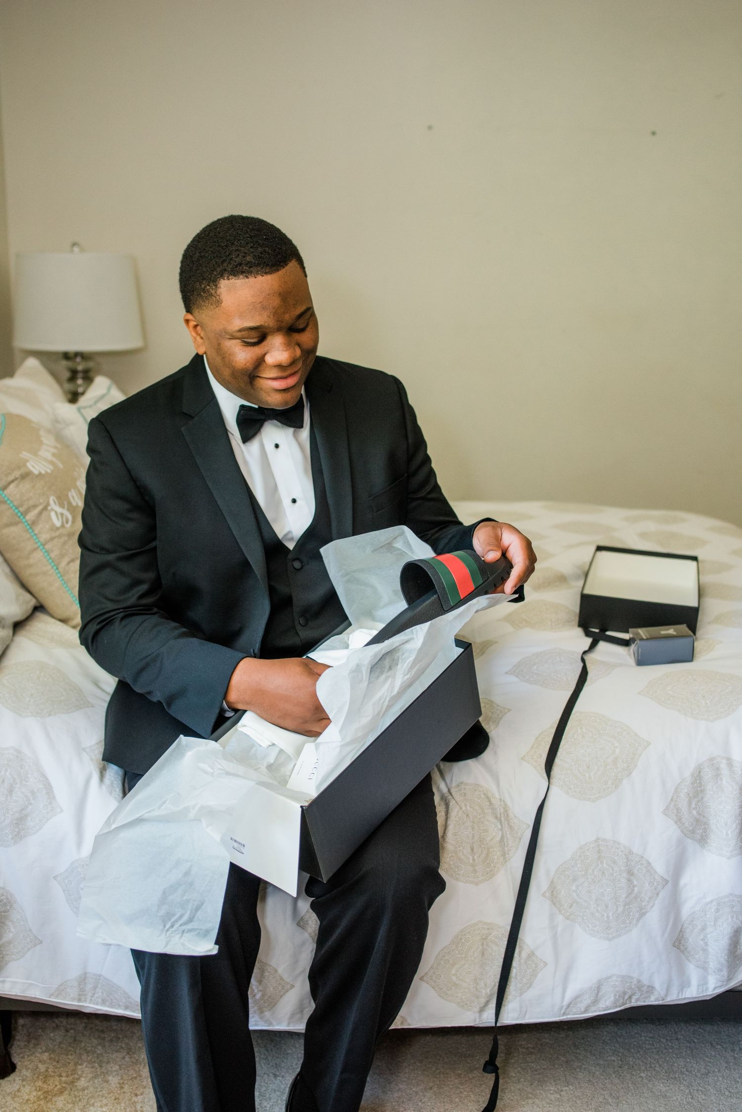 groom smiling opening wedding gift box