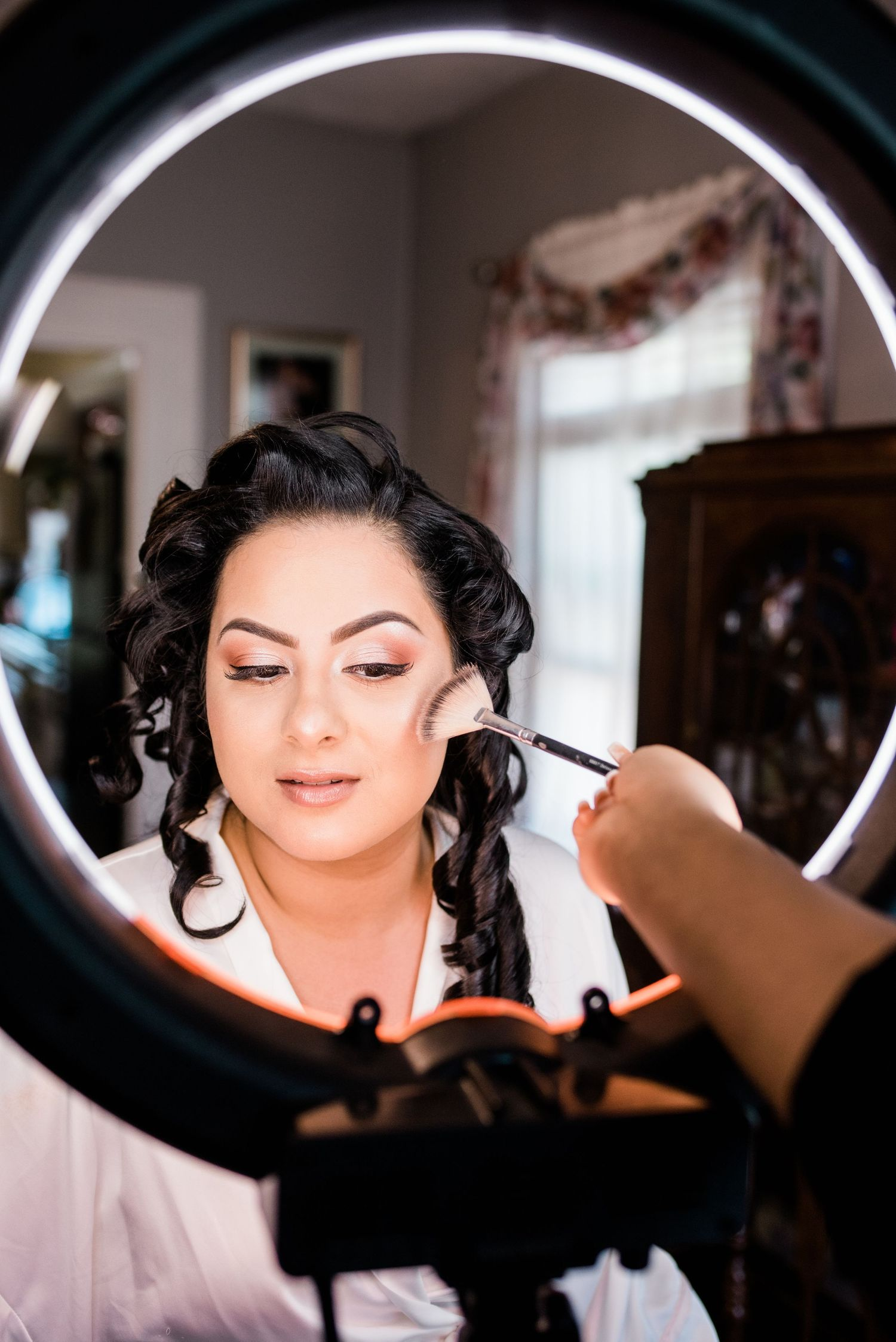 bride getting ready in front of a ring light