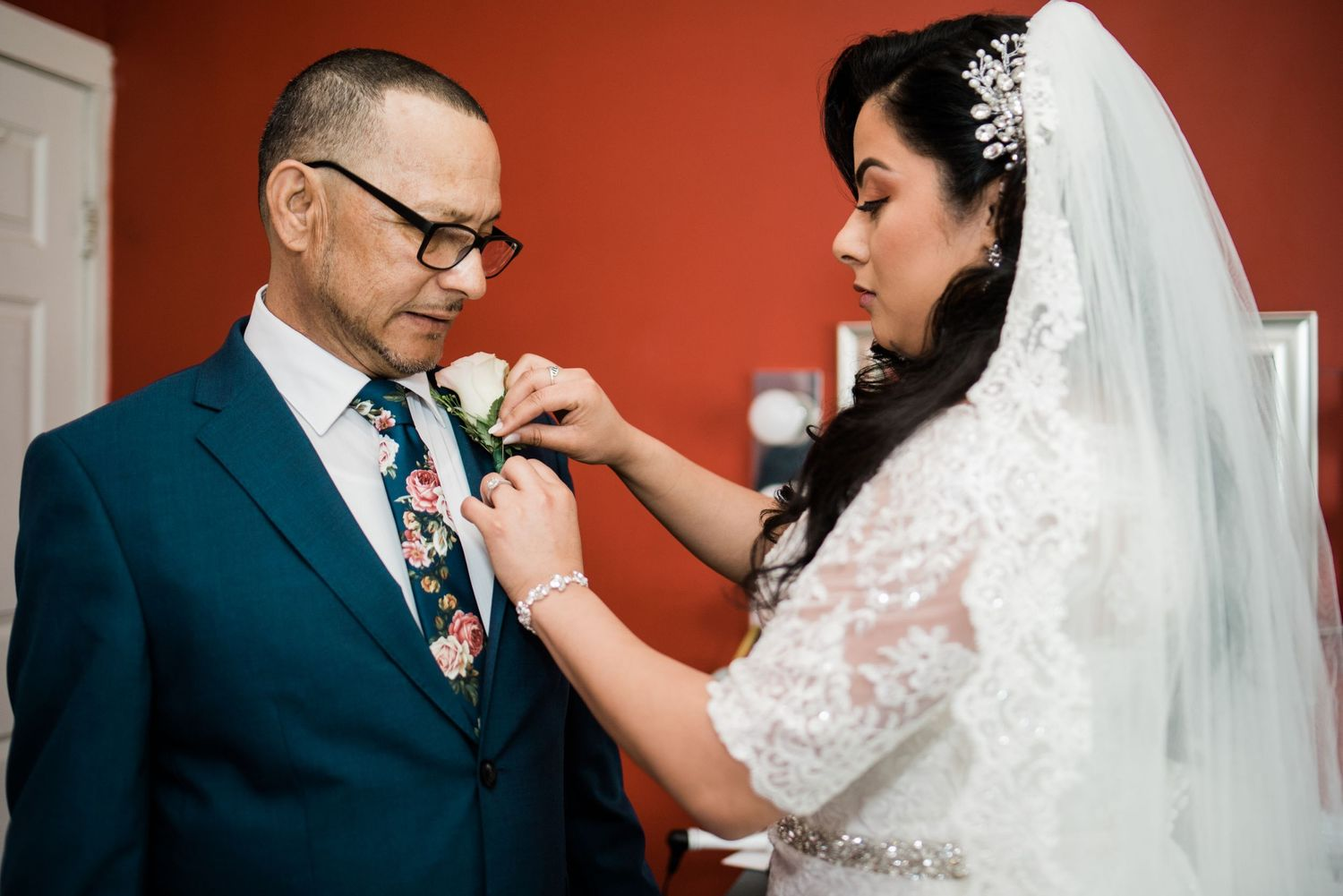 bride putting boutonnière on dad
