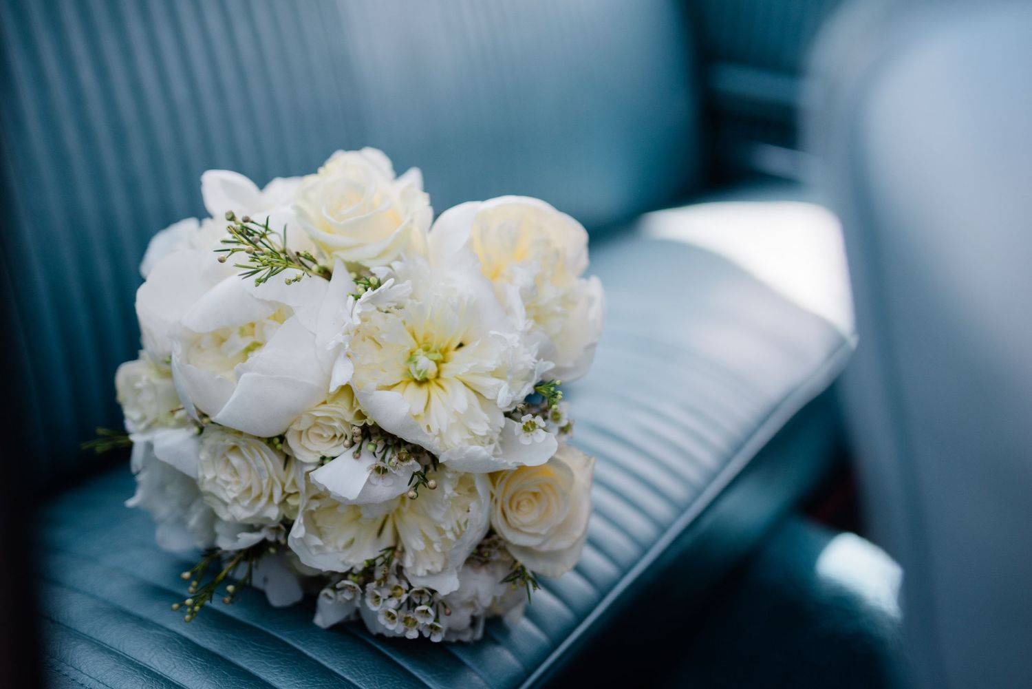 wedding bouquet on back seat of vintage car