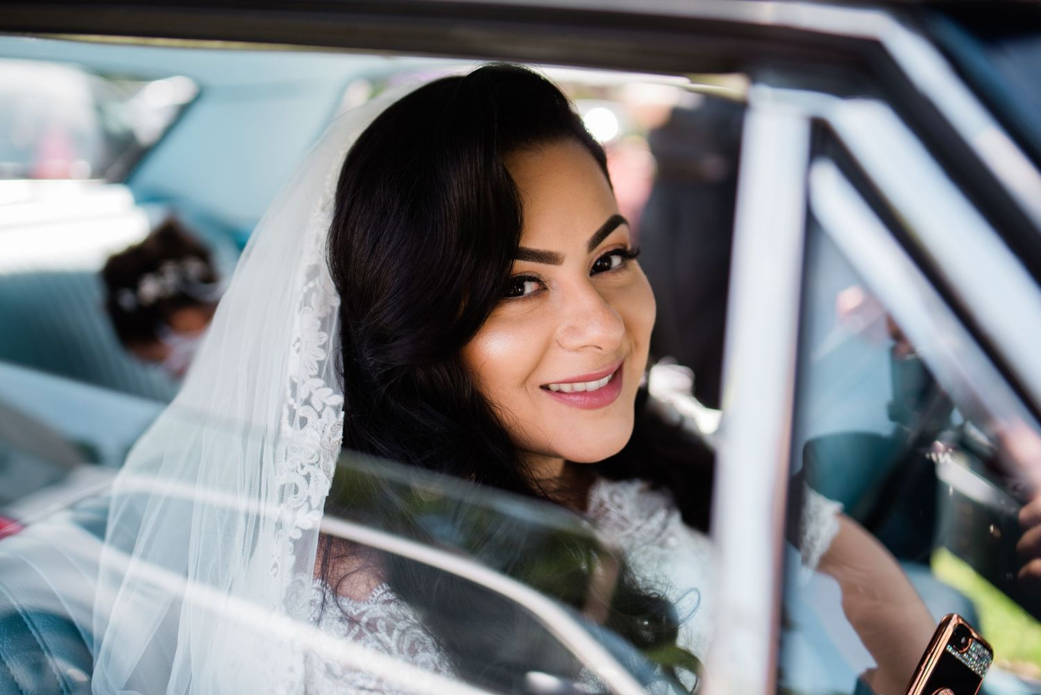 bride smiling sitting inside vintage car