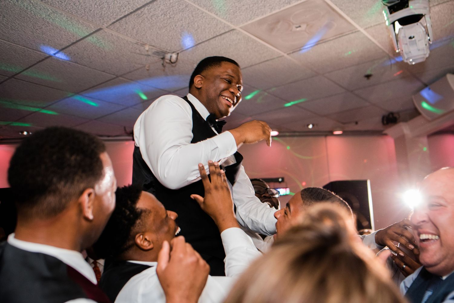 groom being picked up by wedding guest on the dance floor