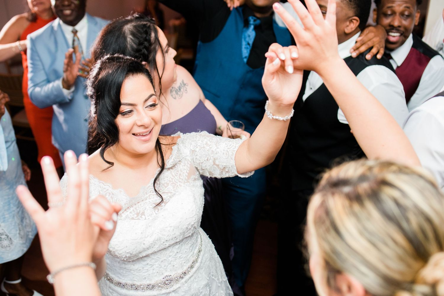 bride dancing with hands up in the air in the dance floor