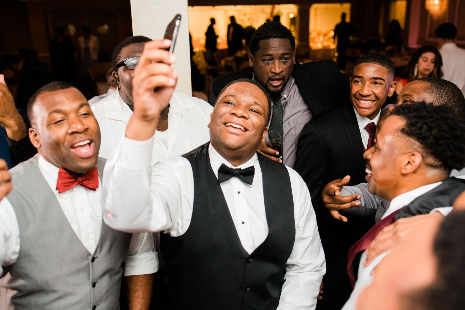 groom taking a selfie with this friends on the dance floor