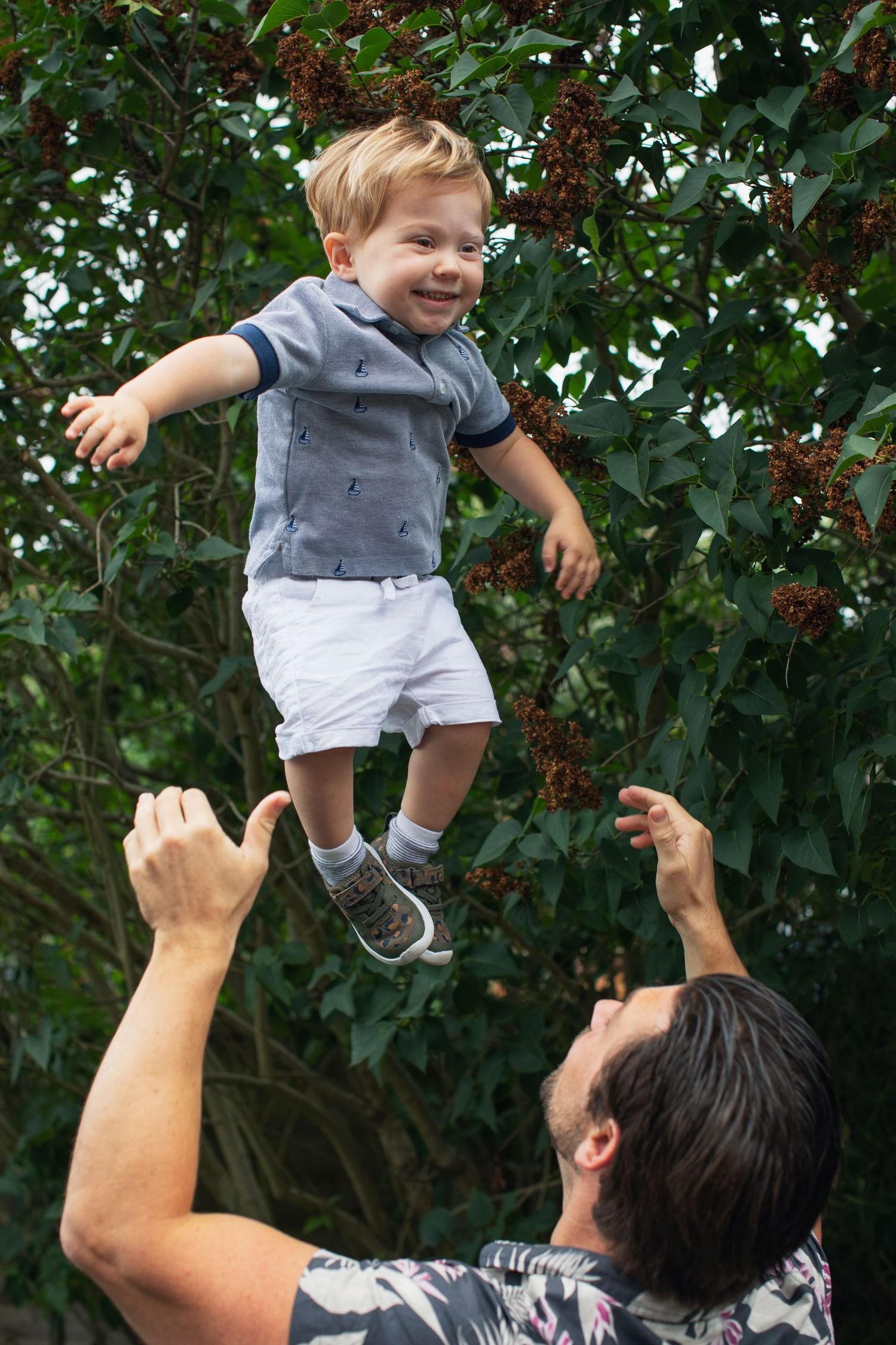 small boy being thrown up in the air by his father