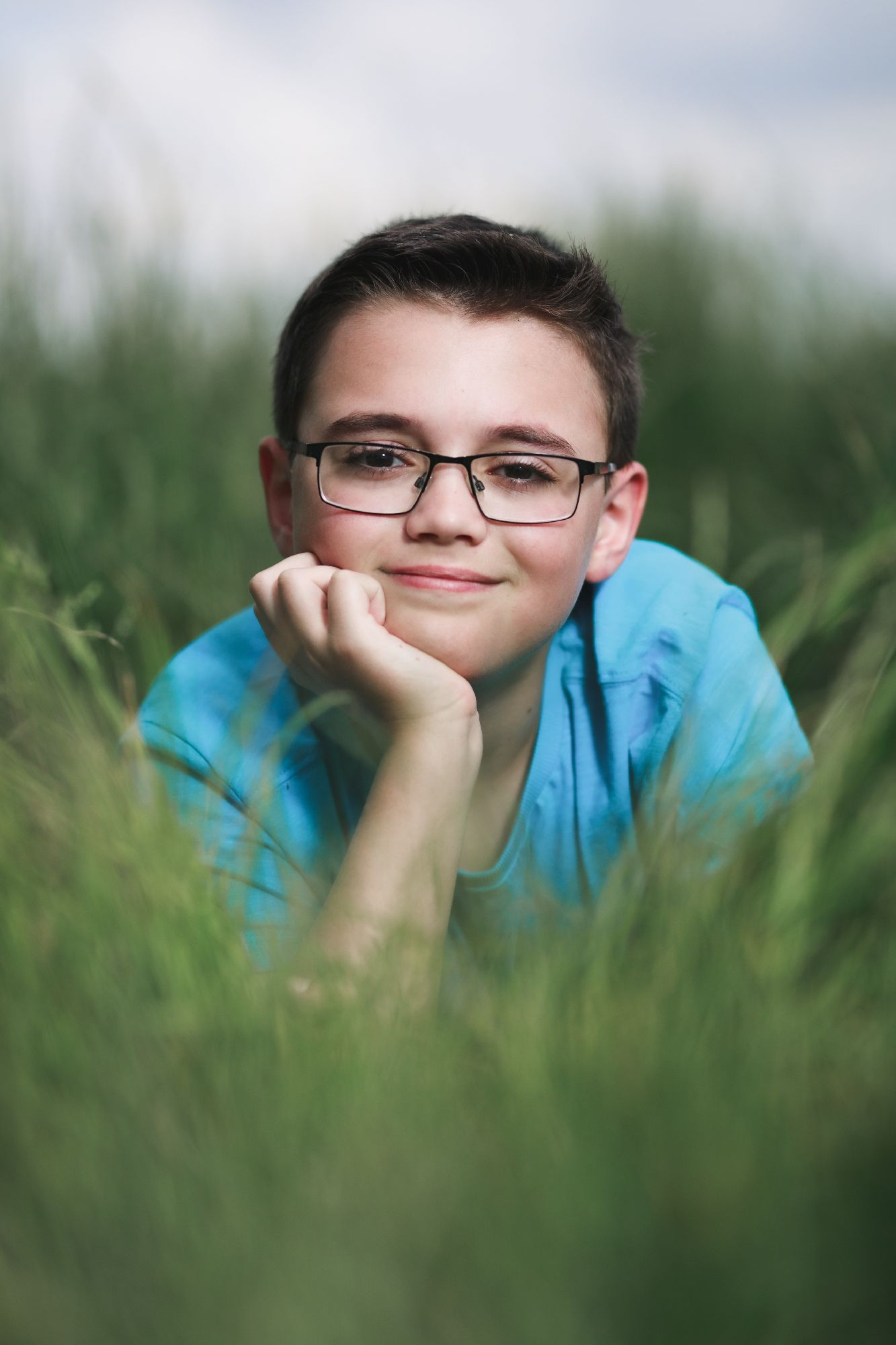 boy laying in long grass