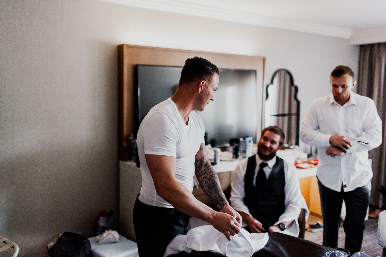 groom putting on white button up preparation for wedding day