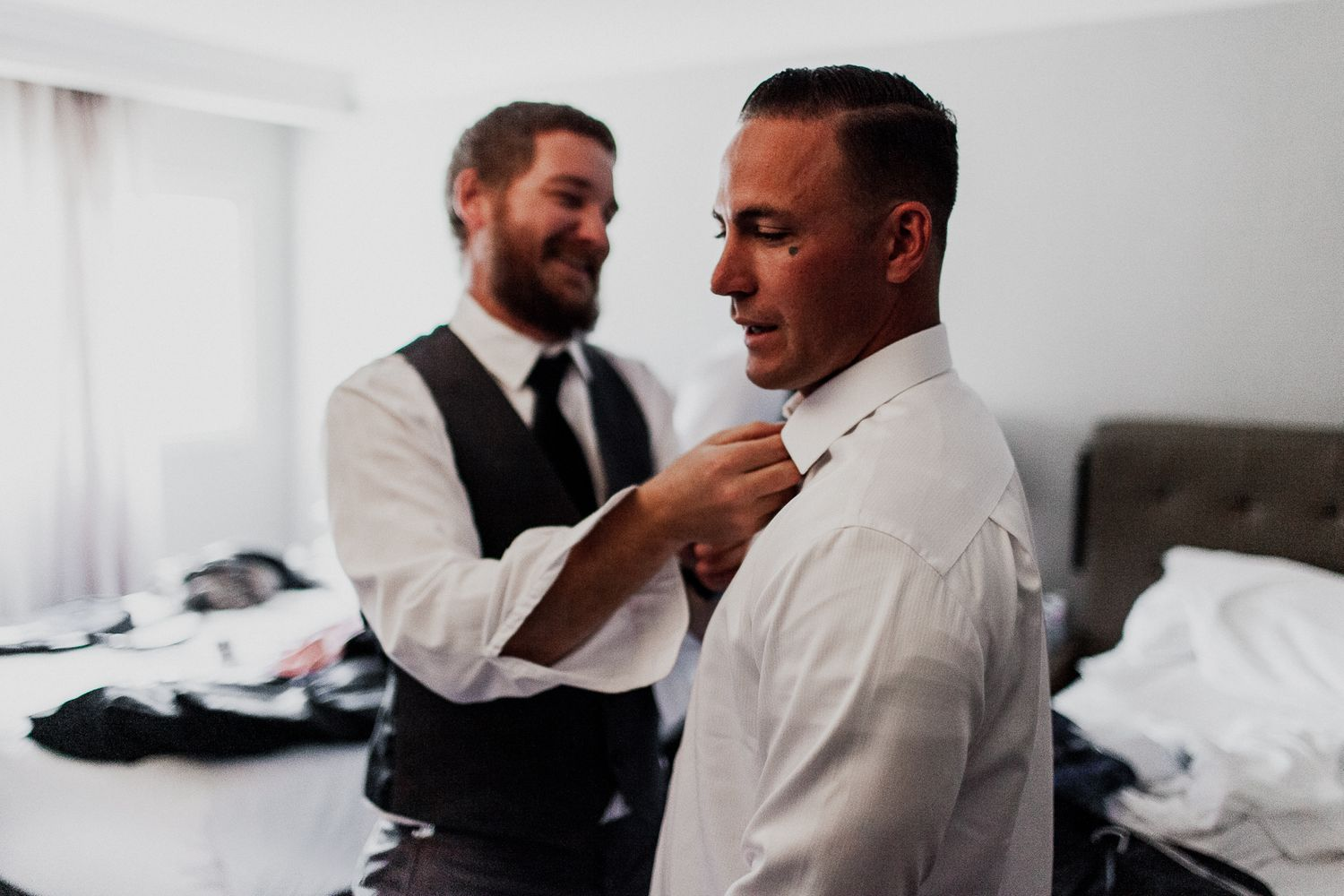 best man helping groom with button