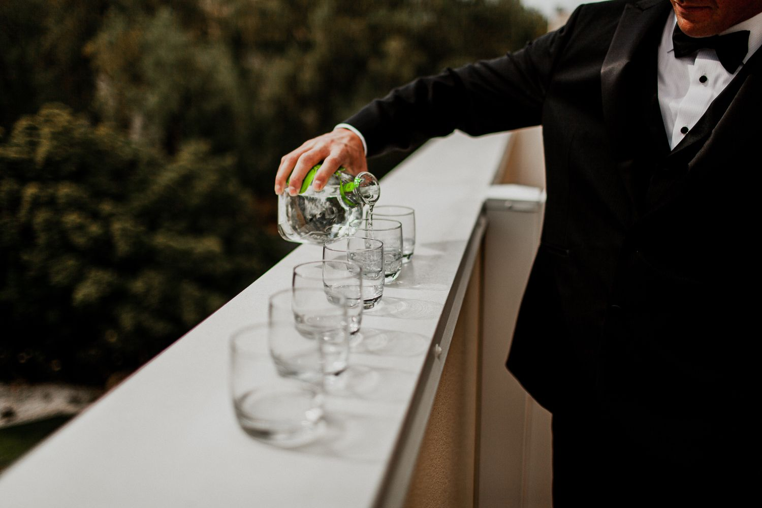 groom pouring patron drink in glasses for groomsmen