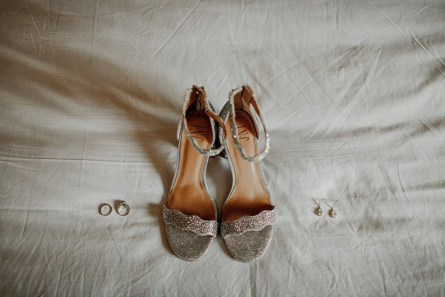 bride shoes, earrings, and rings on top of bed