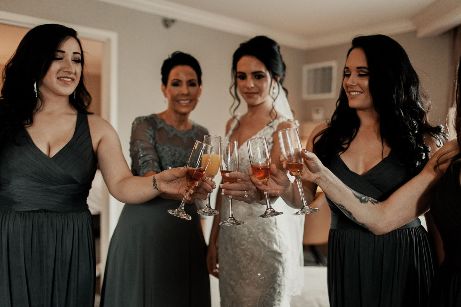 bride and bridal party cheer-sing drinks