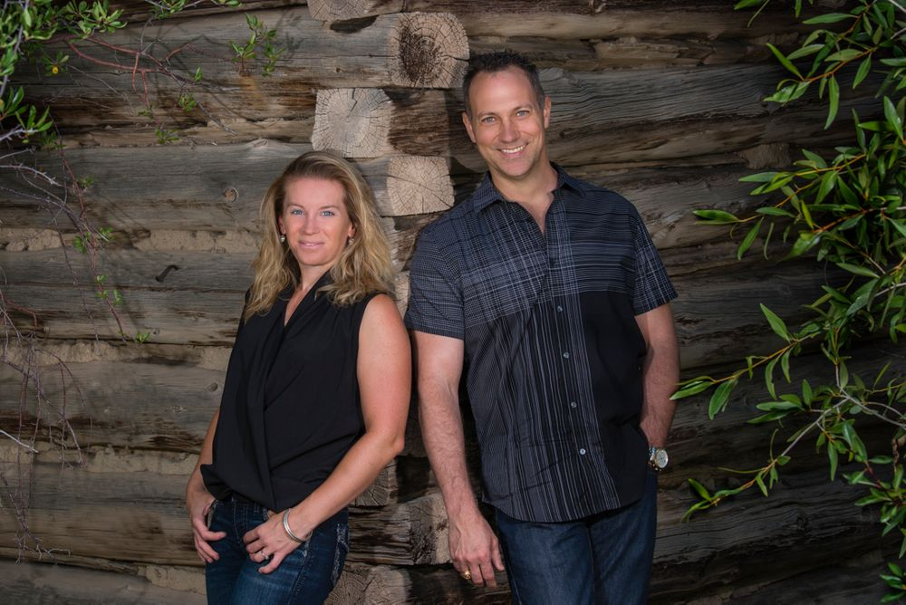 business lifestyle portrait:  Portrait of a woman and a man leaning on a log cabin