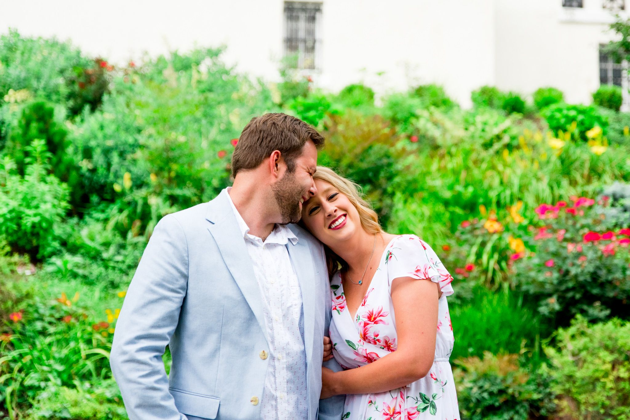 blonde woman hugging arm of man with short brown hair on a rainy day in Louisville for engagement pictures