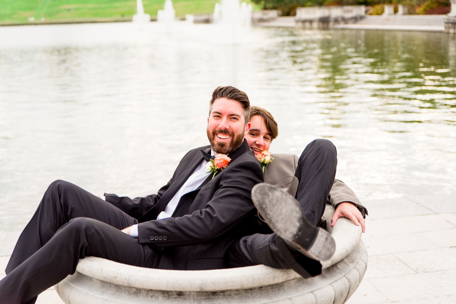 groom and groomsmen sit in bird bath at STL Forest Park groomsmen portraits
